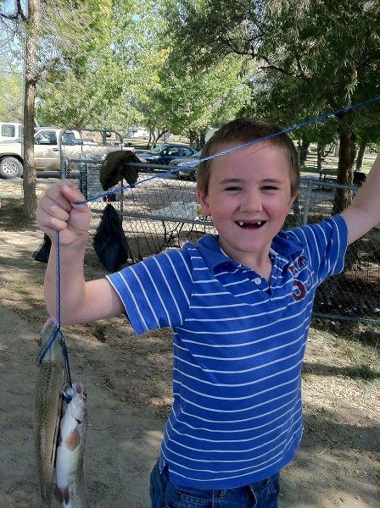 Boy-shows-off-fish-at-Green-River-fishing-event-by-B.-Stettler.jpg
