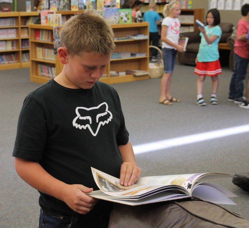 A-student-looks-through-a-book-that-he-might-want-from-the-Reading-Leveling-program-at-Castle-Heights-Elementary..jpg